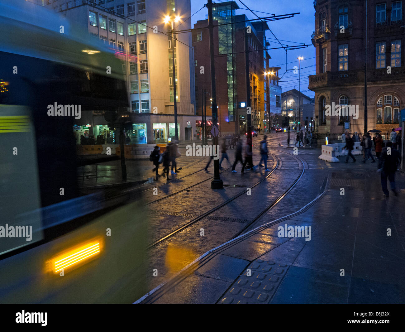 Yellow Manchester trams at dusk, England, UK - Stock Image