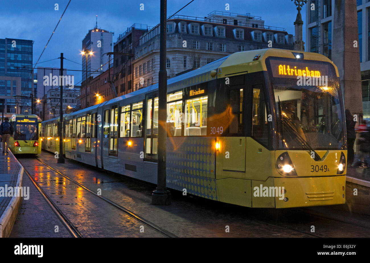 Yellow Manchester trams at dusk, England, UK Stock Photo