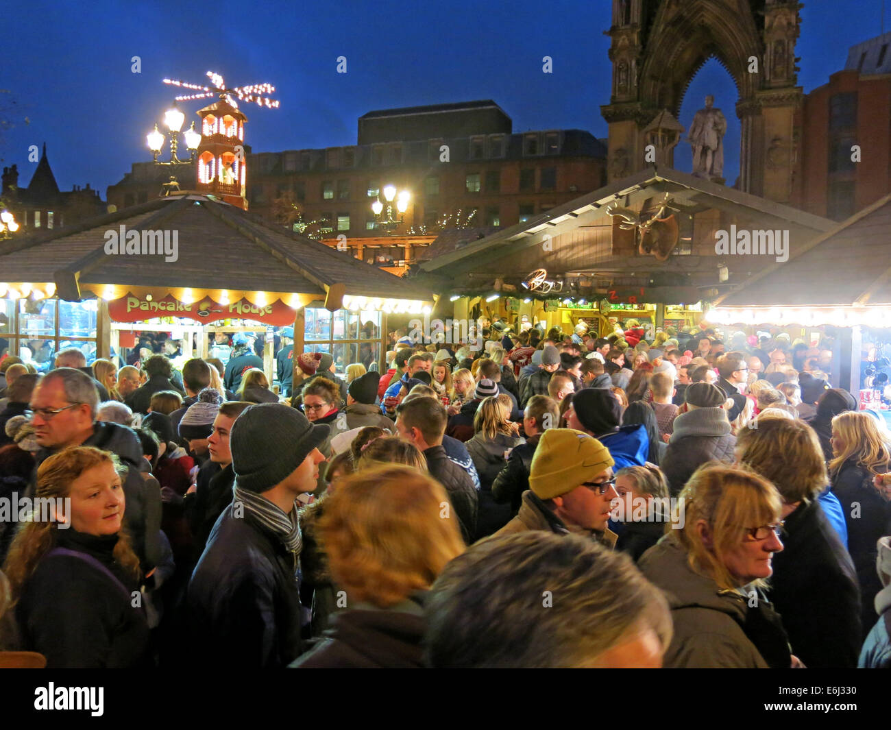 Visitors & shoppers enjoying Manchester Christmas German Markets in Albert Square , December at dusk - Stock Image