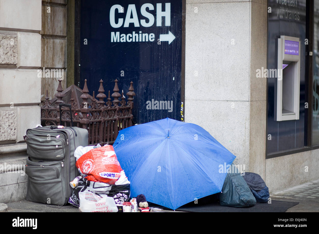 Homeless sleeping in Shop window with belongings beside them in the rain London England - Stock Image