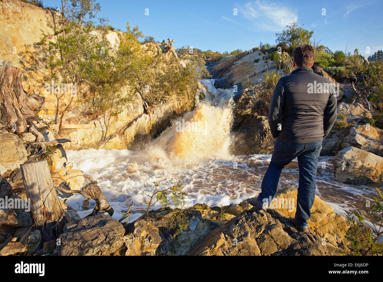 Man standing looking at a waterfall - Stock Image