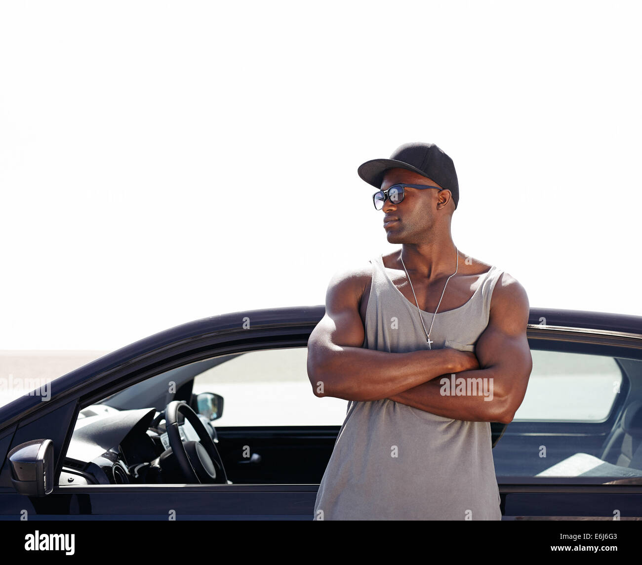 Image of young african man standing by his car. Muscular male model wearing sunglasses and cap outdoors. - Stock Image