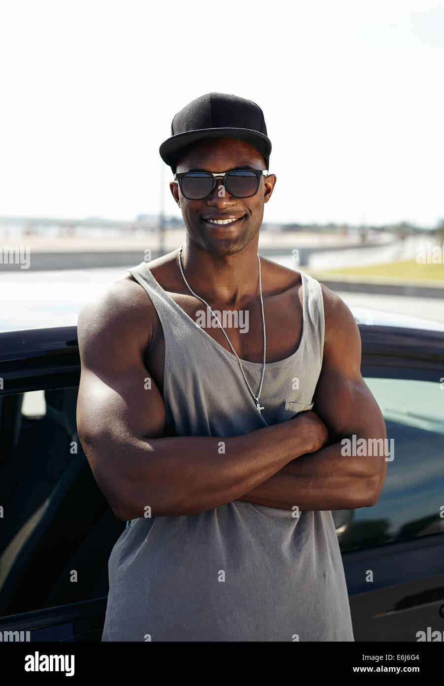 Portrait of handsome African guy with his arms crossed leaning against a car smiling. Stylized muscular guy wearing - Stock Image