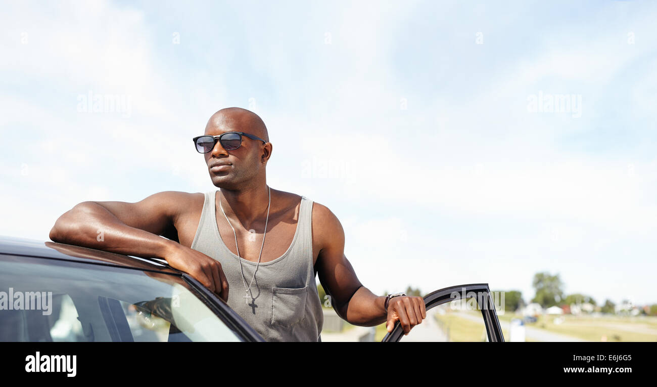 Handsome young guy leaning on car. African male model wearing sunglasses standing by his car looking away with door - Stock Image