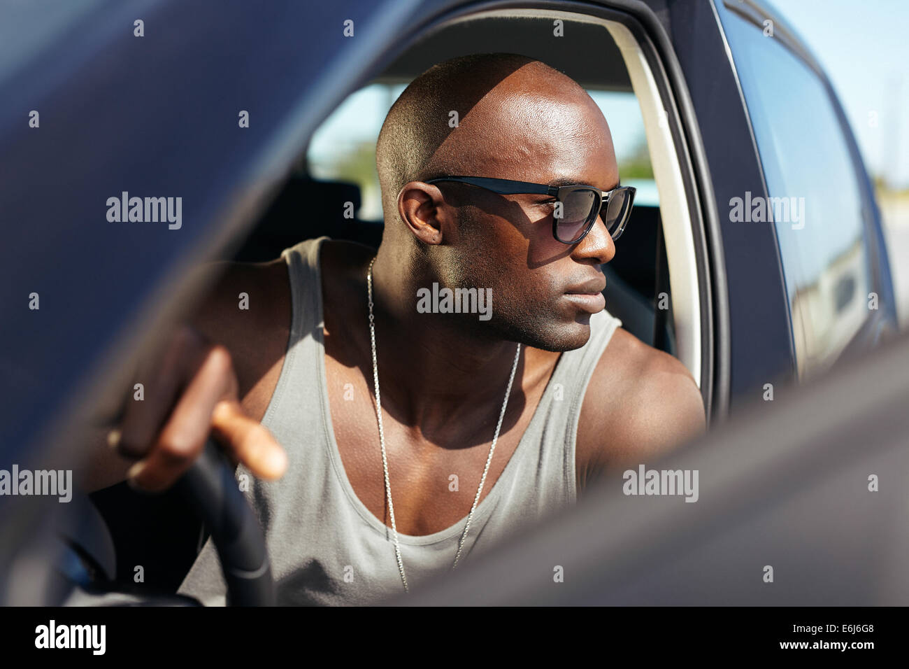 African male model in his car. Stylish young man with hands on steering wheel. Muscular young wearing sunglasses - Stock Image