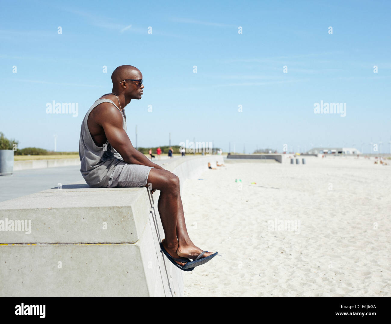 Side view of young african man sitting on a beach promenade looking away. Afro american model relaxing outdoors - Stock Image