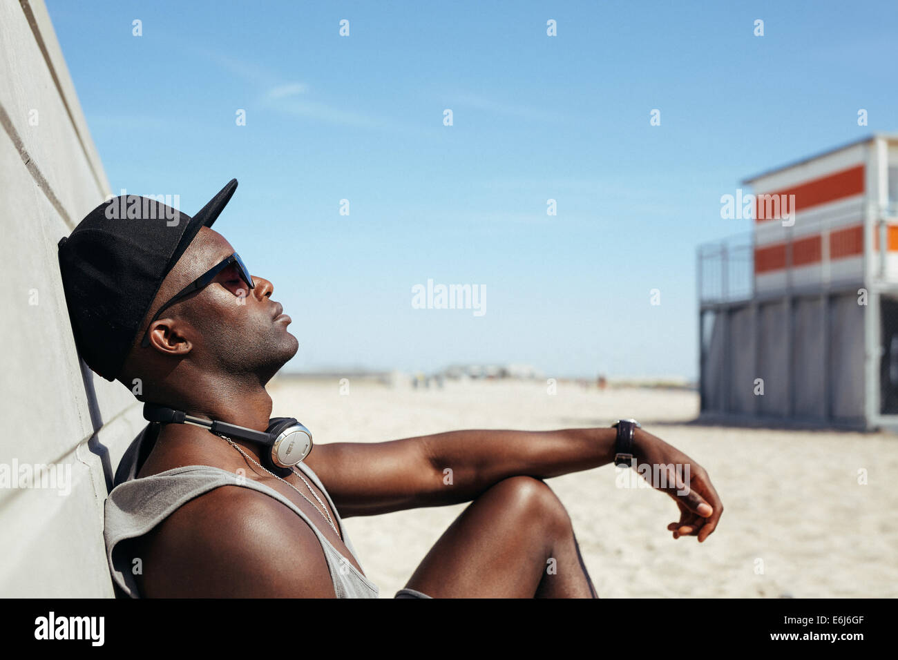 Side view of relaxed African man leaning to a wall at beach sunbathing. Black guy wearing sunglasses and cap relaxing. - Stock Image