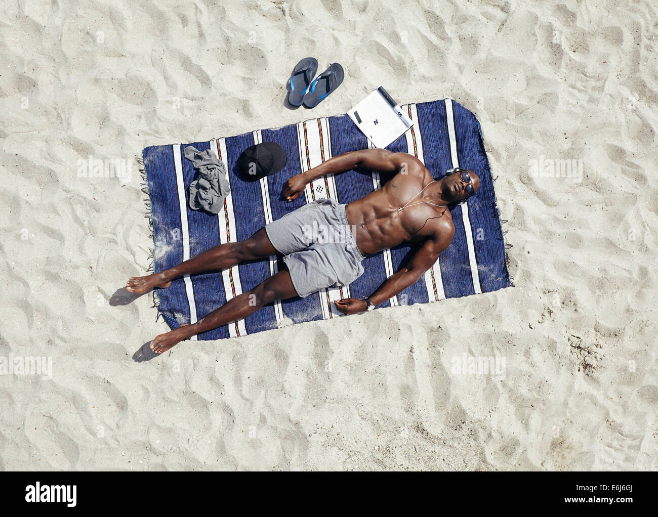 Top view of young guy lying shirtless on a mat sunbathing. African male model relaxing on beach on a hot summer - Stock Image