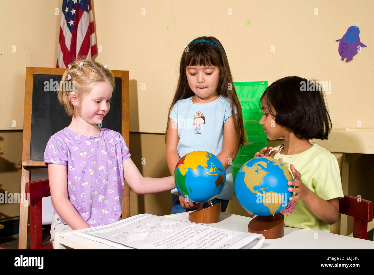 multi ethnic racial diversity racially diverse multicultural cultural  Girls work working together study globe map Stock Photo