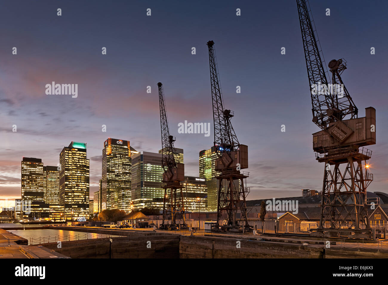 Canary Wharf, London Docklands with old dock cranes in foreground in at night. - Stock Image