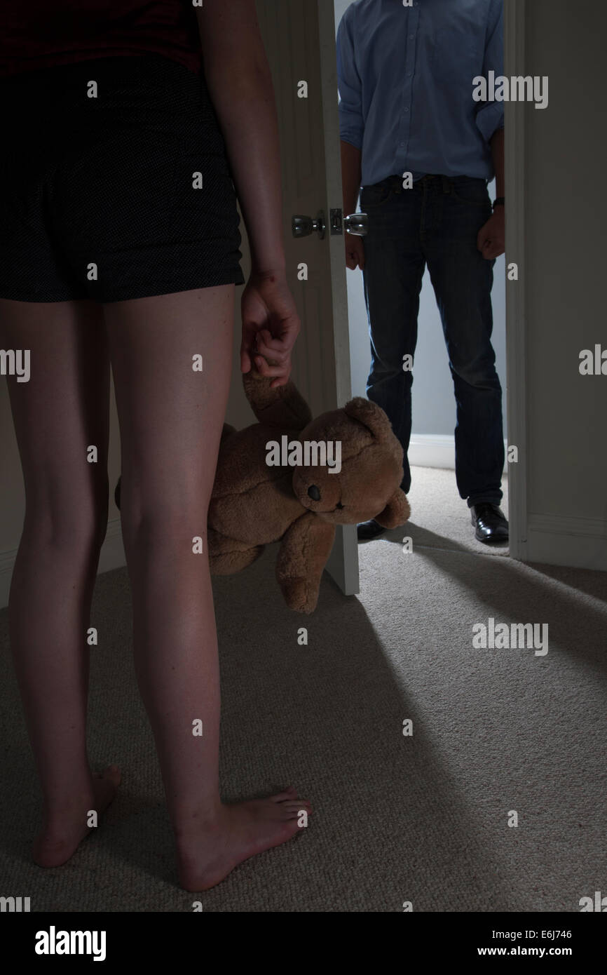 Anonymous man entering a dark room, a young girl standing in the foreground looking towards the man holding a teddy - Stock Image