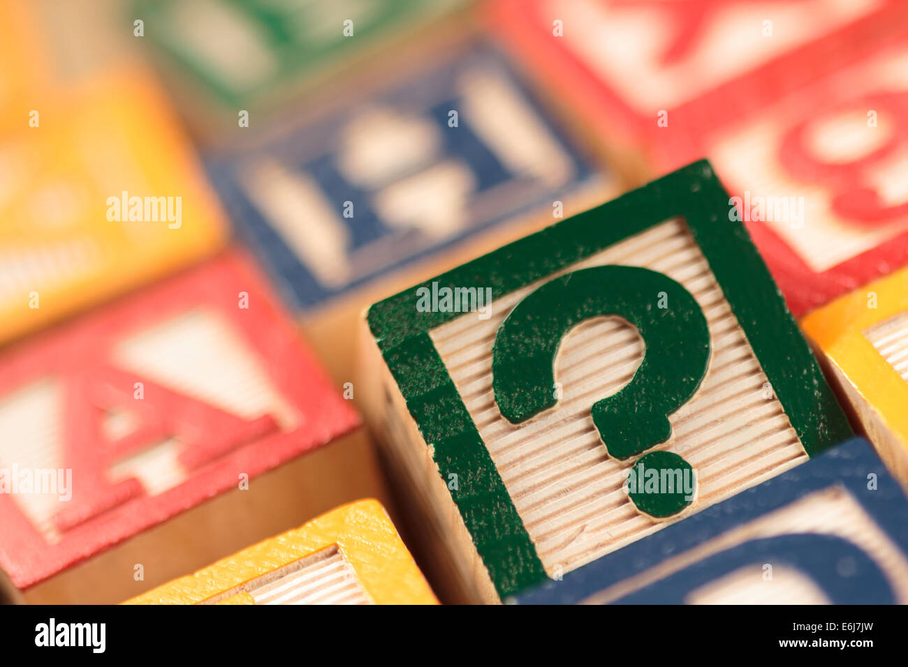 Wooden, colorful educational blocks with selective focus on question mark. - Stock Image
