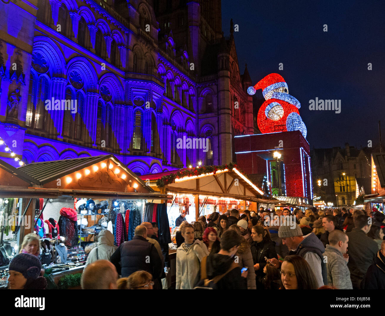 Manchester December Christmas Market at dusk, with Santa on town hall, Albert Square, England, UK - Stock Image