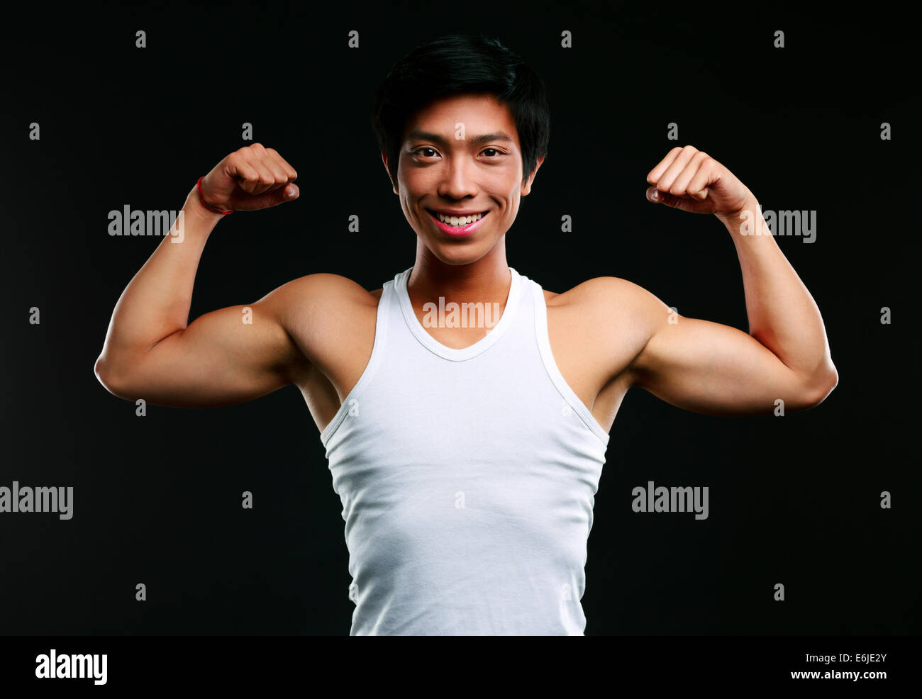Smiling asian muscular man with arms stretched out on black background Stock Photo