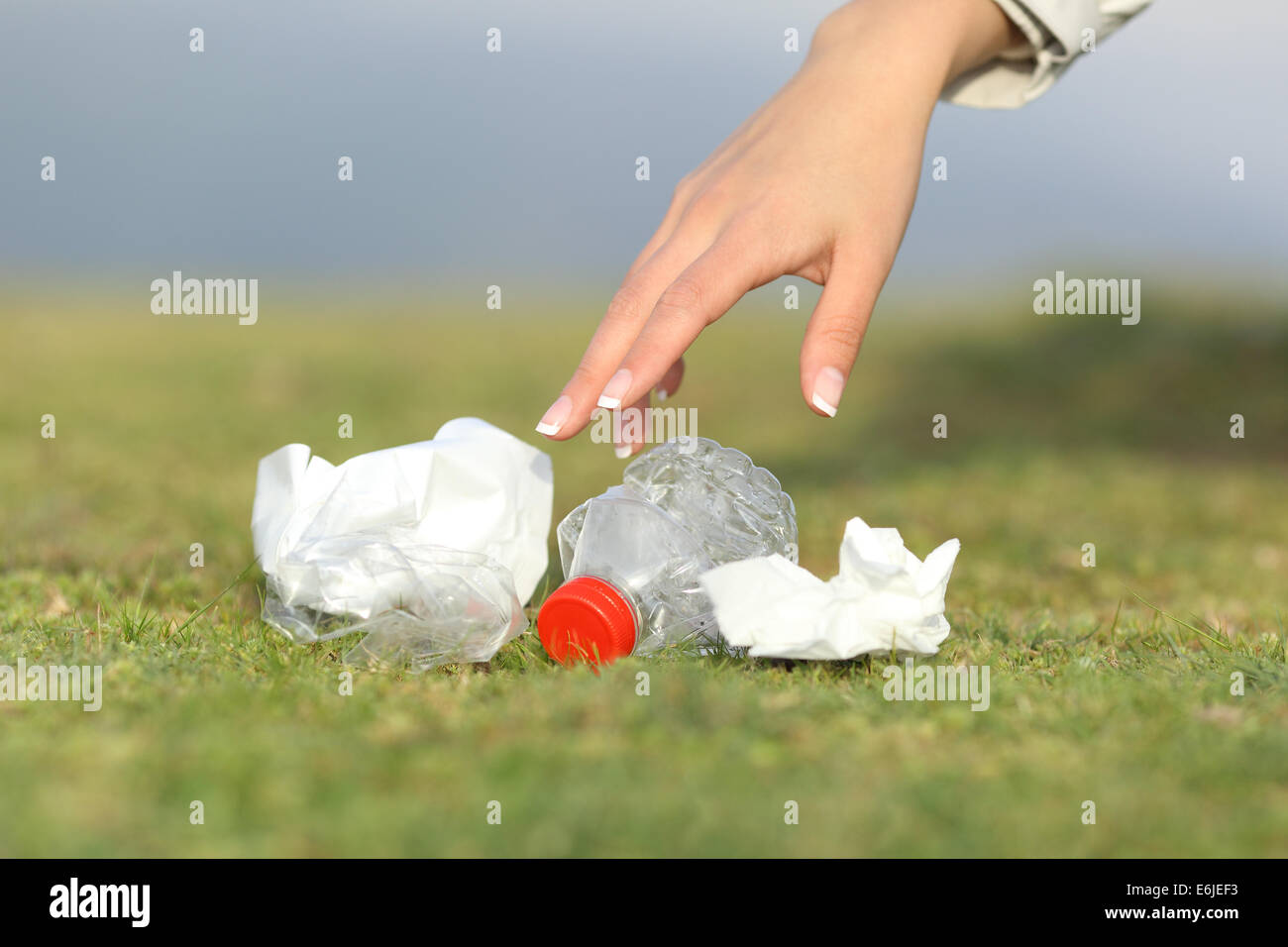 Woman hand collecting garbage of the grass in the mountain with copy space - Stock Image