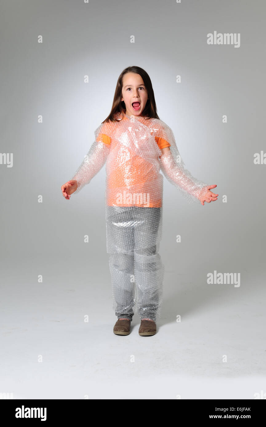 EDITORIAL ONLY - Over protection parenting helicopter parents kid wrapped in bubble wrap to protect from hurt or - Stock Image