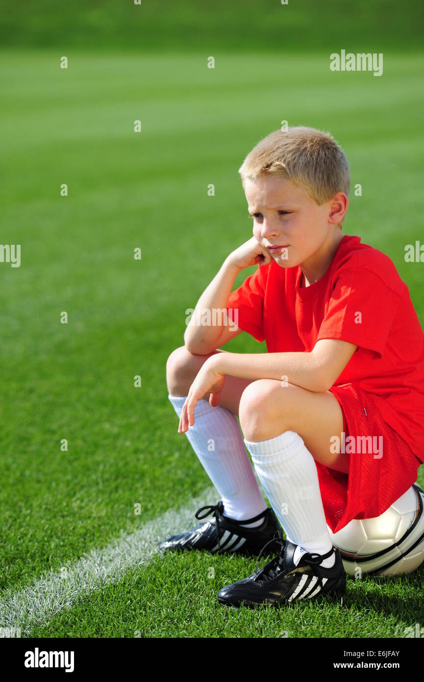 Boy 9 10 11 playing football futbol soccer on grassy pitch field not getting to play - Stock Image