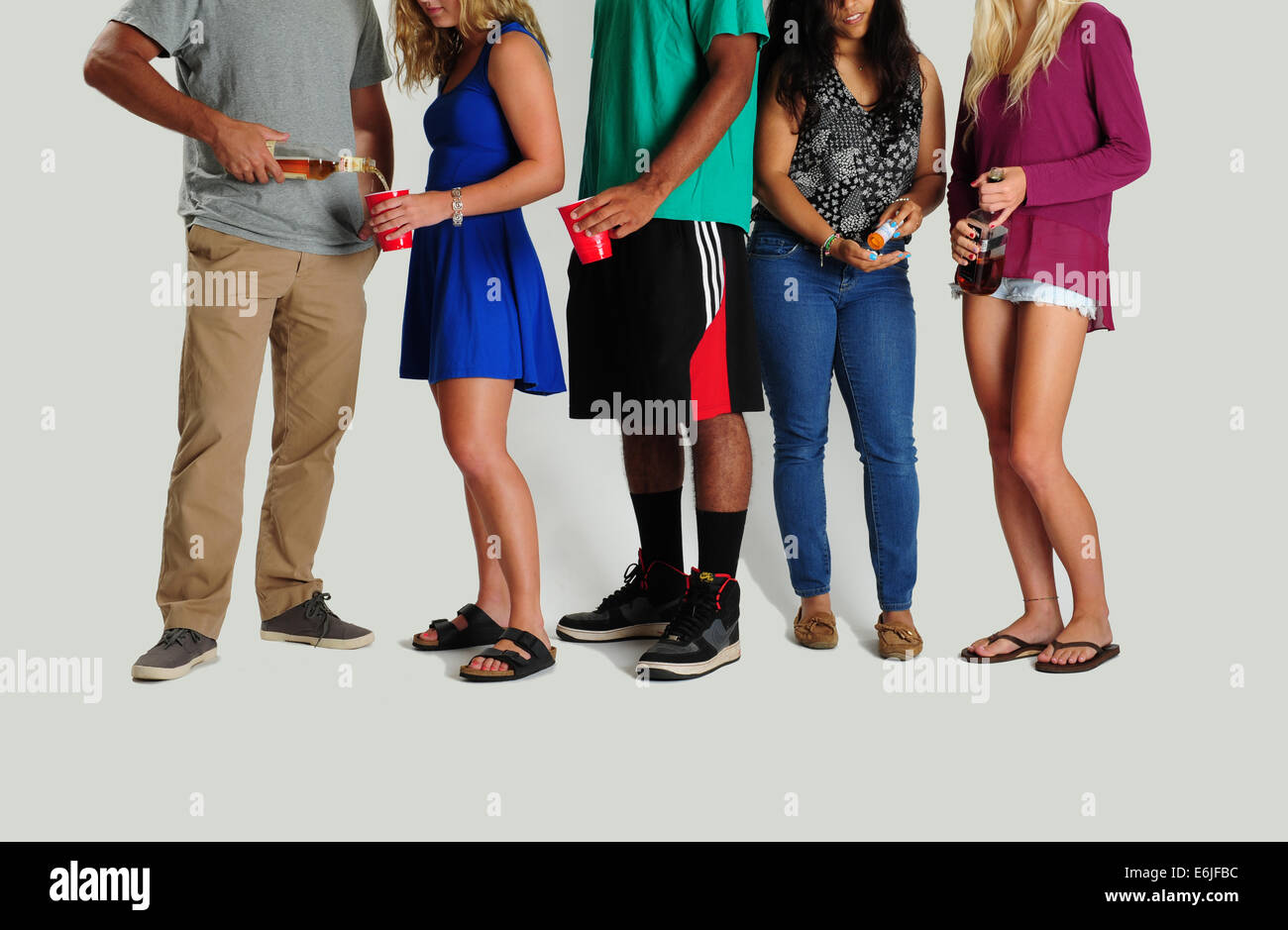 USA Underage alcohol use and drug use - Teens party drinking and taking drugs pills sharing - Stock Image