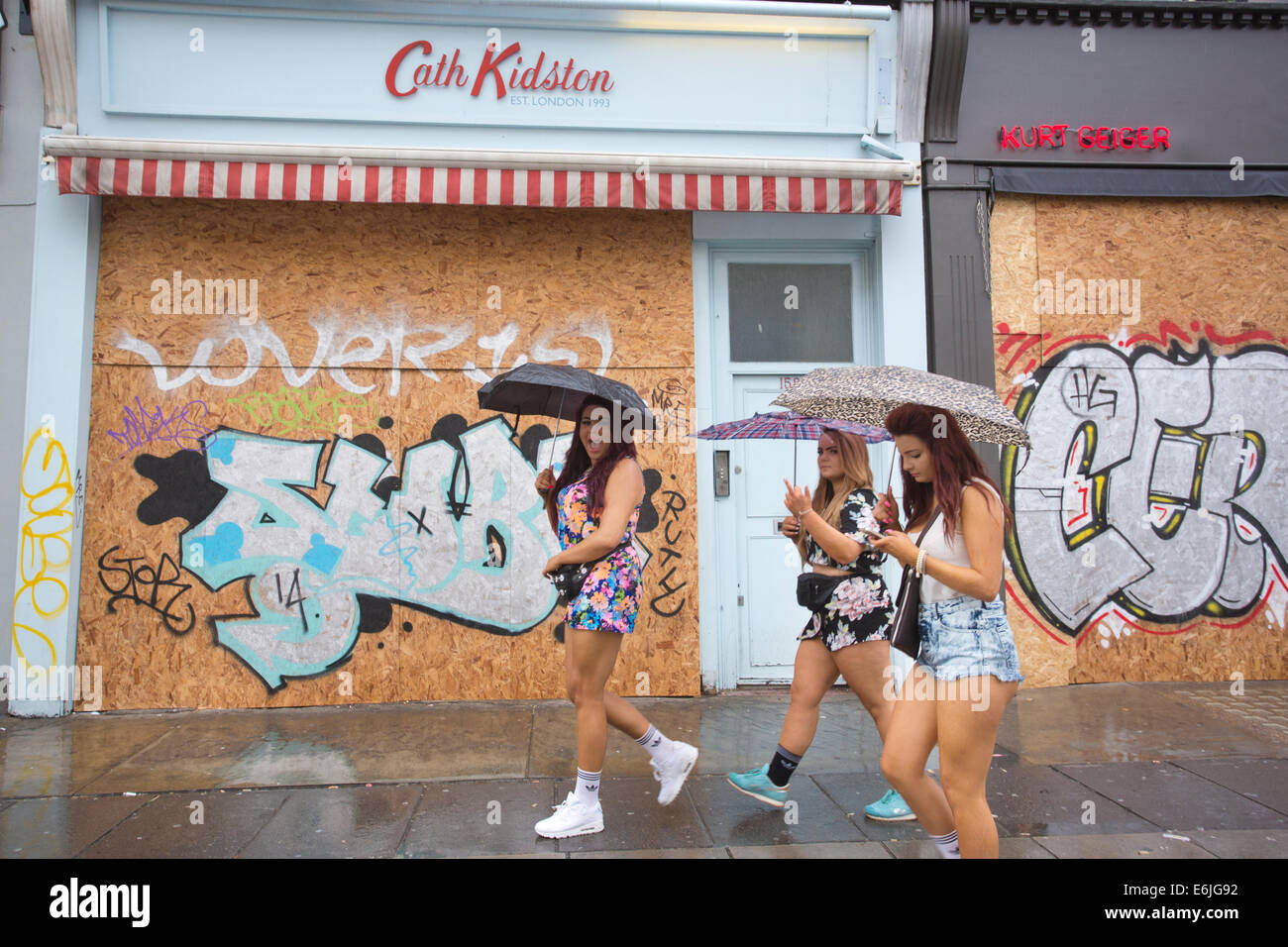 London, UK. 25th Aug, 2014. Carnival goers on a wet August Bank Holiday in the rain at The Notting Hill Carnival - Stock Image