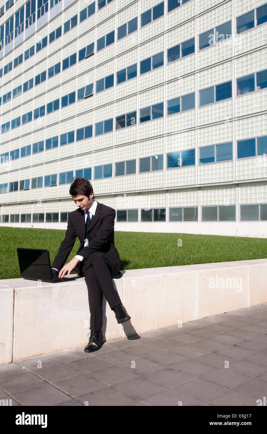 Young executive working outdoors with laptop in the company garden - Stock Image