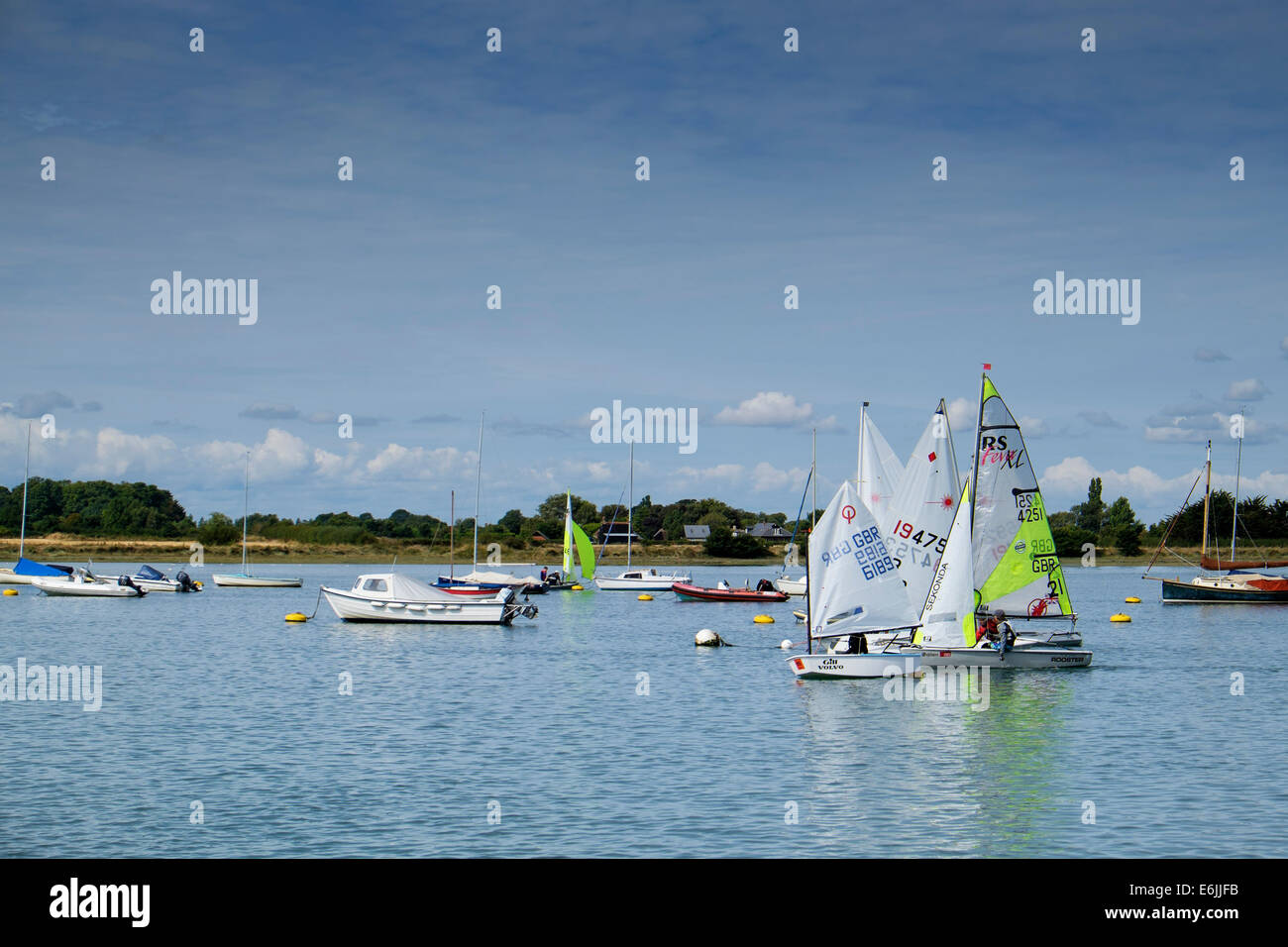 people enjoying their leisure time by sailing in small dinghies in the relative safety of the calm waters in chichester - Stock Image