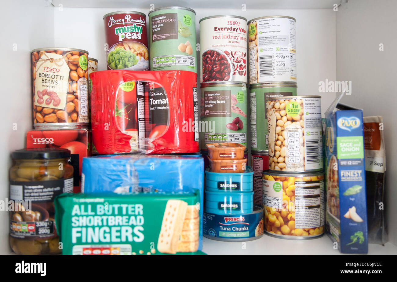 Tinned food produce in a kitchen cupboard UK - Stock Image