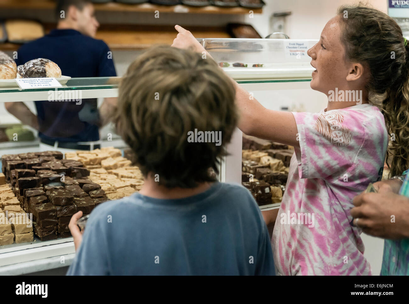 Kids making a selection in a fudge shop. - Stock Image