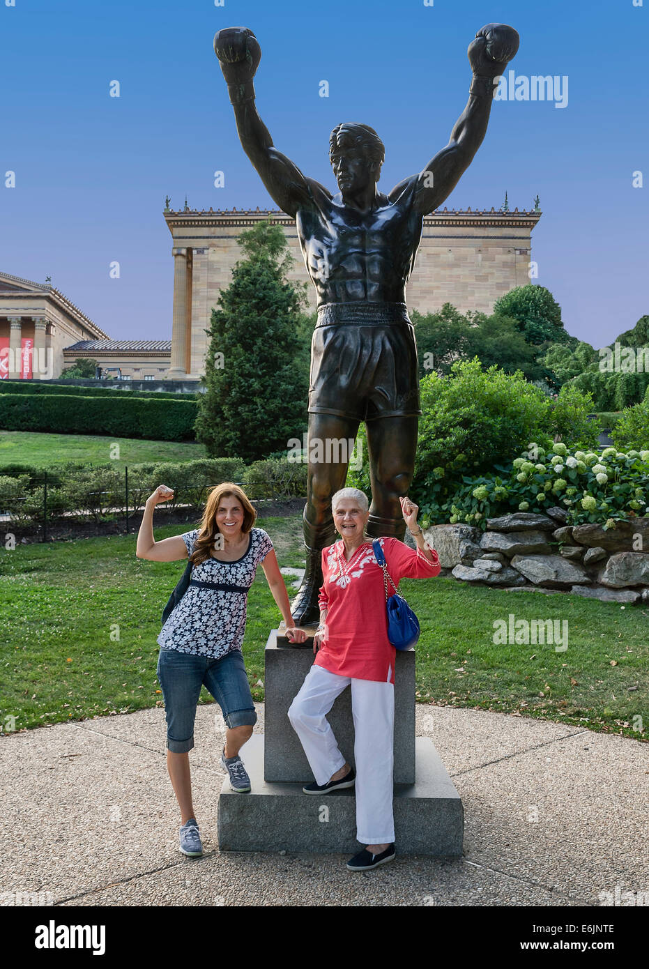 Tourists pose with the Rocky statue in from of the Philadelphia Museum of Art. - Stock Image