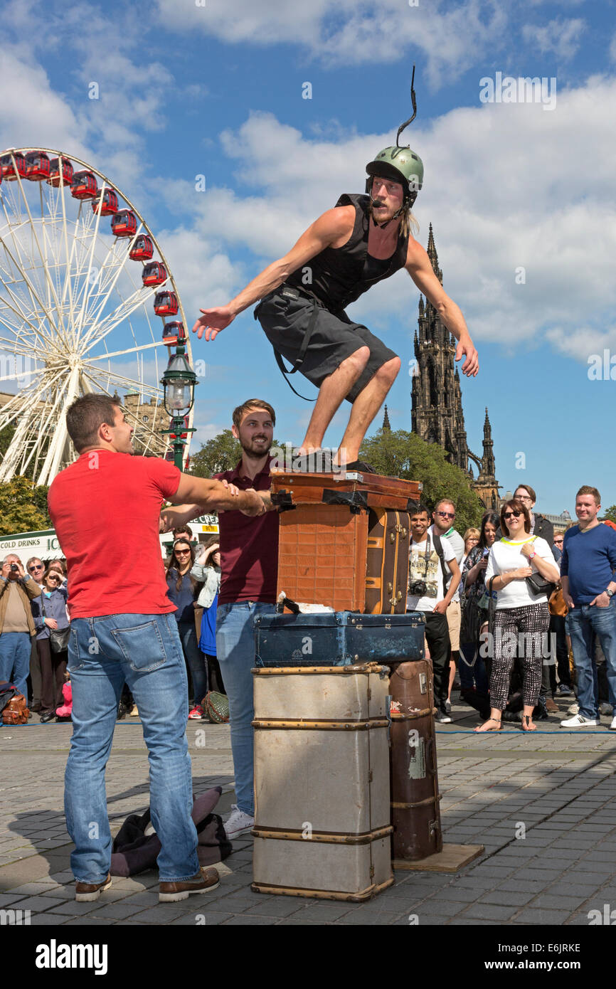 Acrobat performing his balancing act, with the help from two men from the audience, at The Mound, Edinburgh Fringe - Stock Image