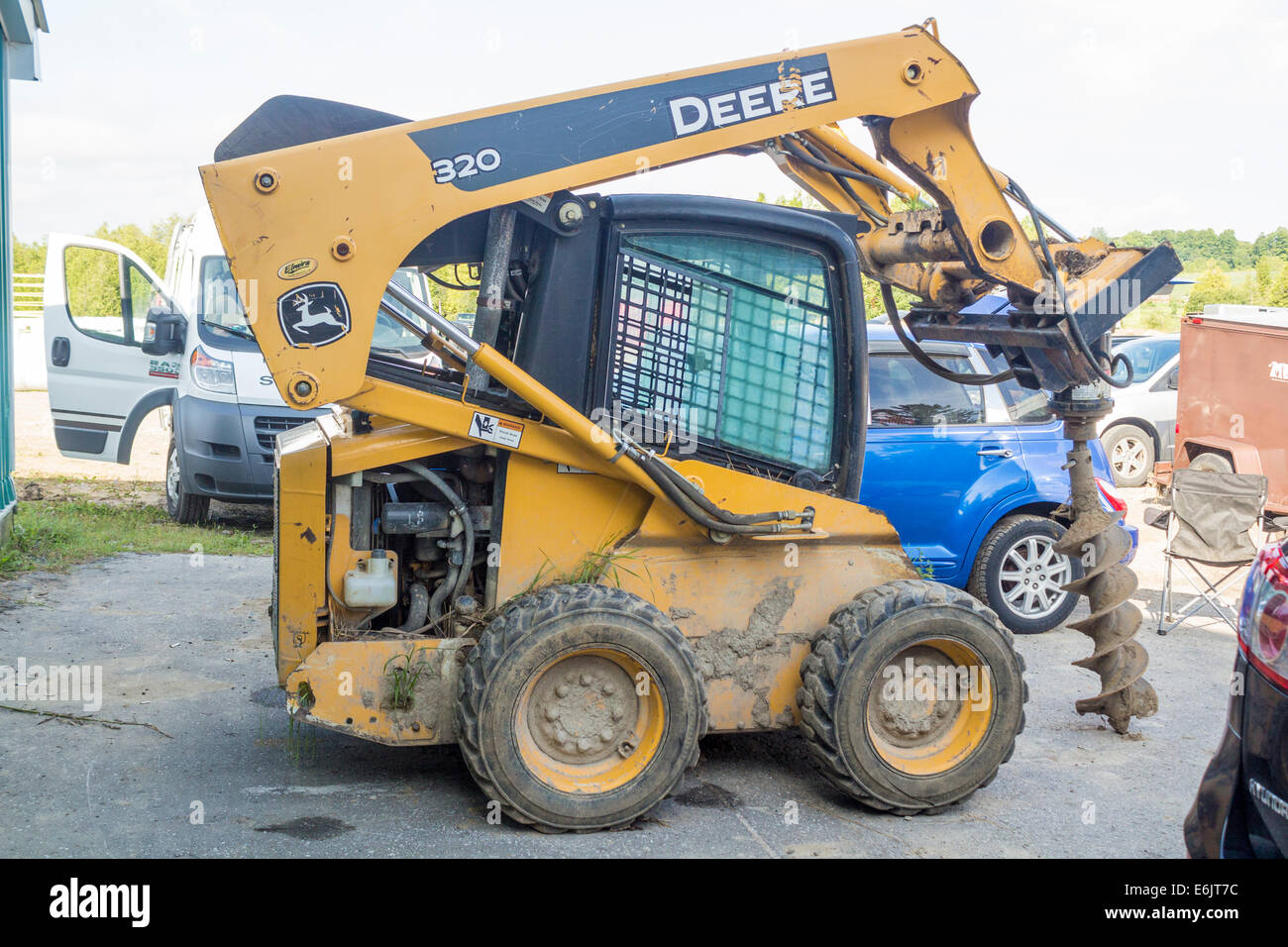 Johm Deere skid steer with attached auger. - Stock Image