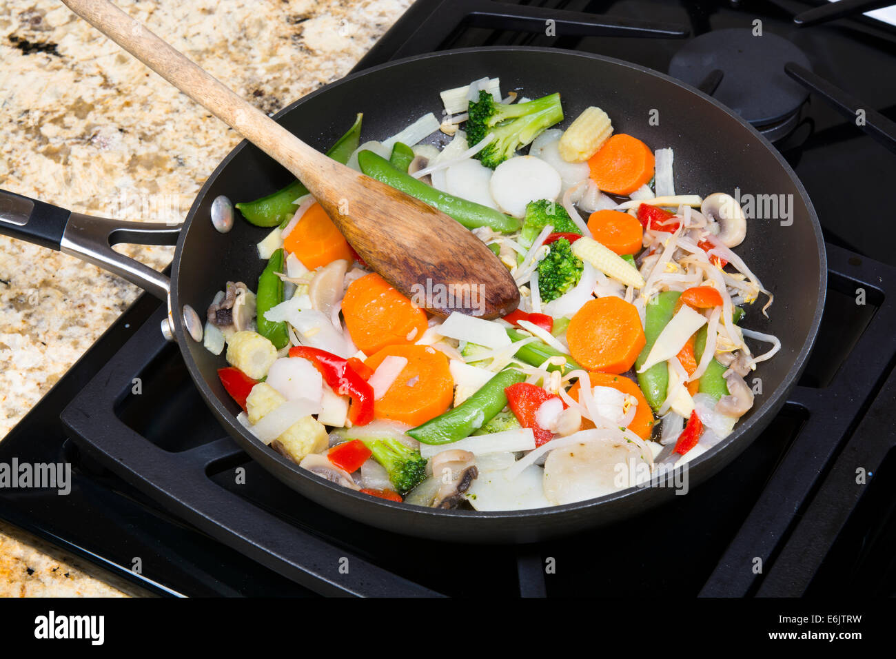 Fresh mixed vegetable stir fry with onions, carrots, snow peas, red peppers, and sprouts simmering in a stove top - Stock Image