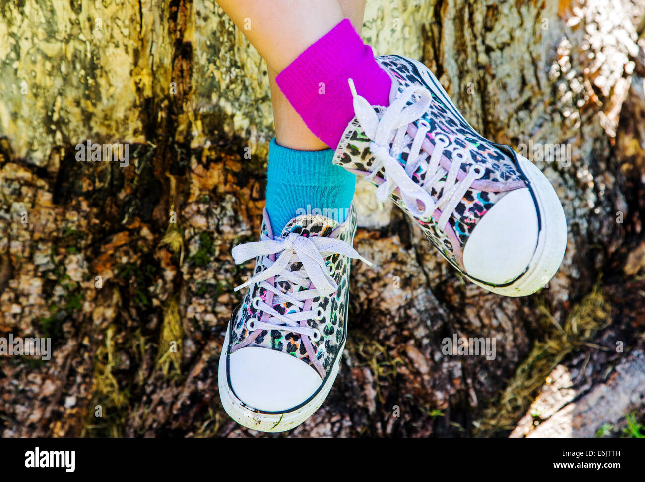 Photograph of seven year old girl's colorful sneakers and two different colors of socks - Stock Image