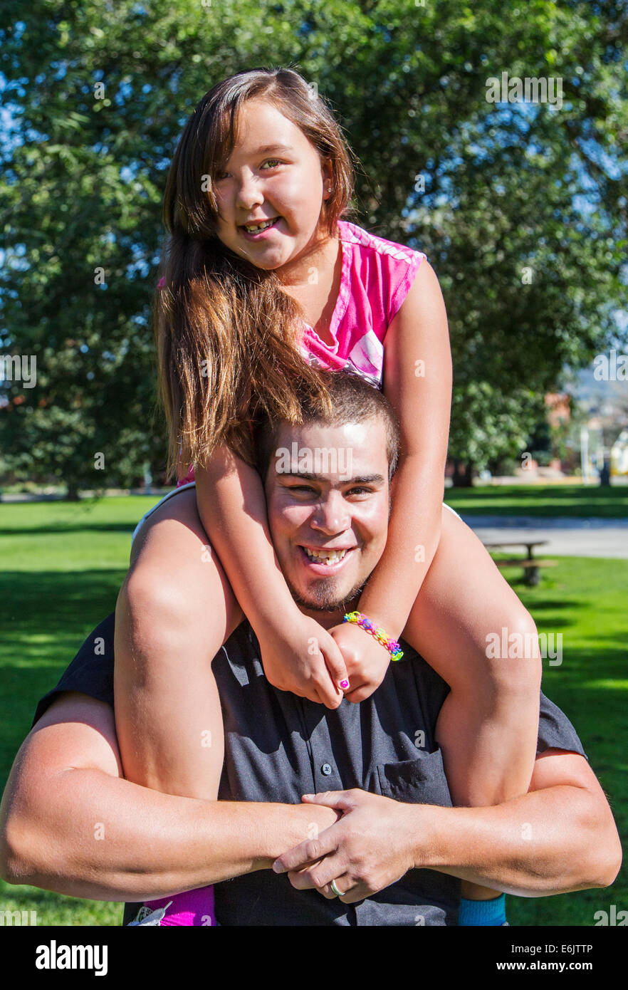 Father holding his seven year old daughter on his shoulders Stock Photo