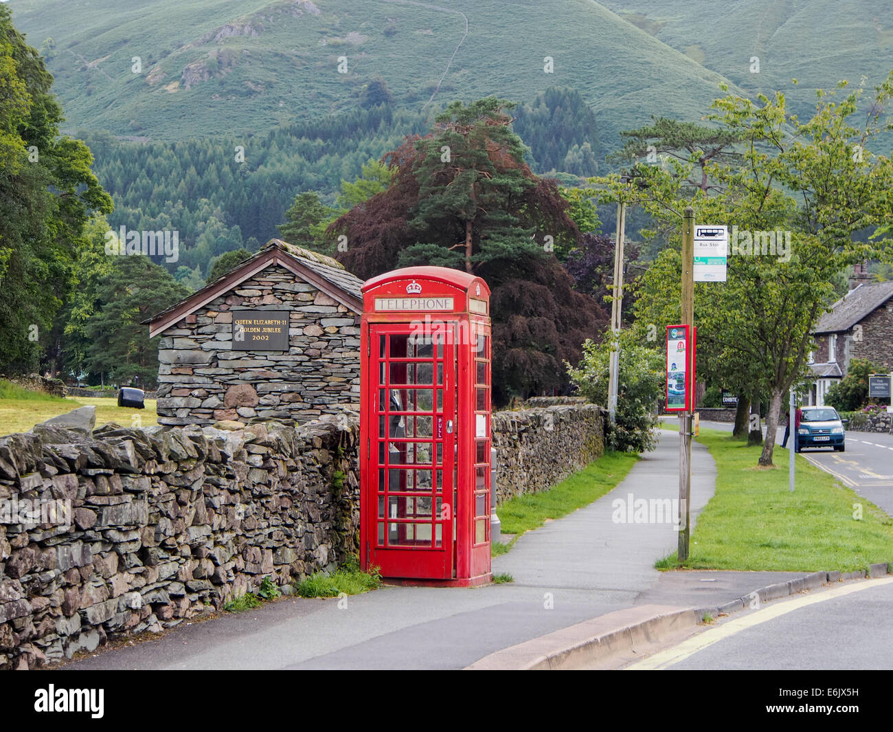 A red telephone box and bus stop in a British rural village - Stock Image
