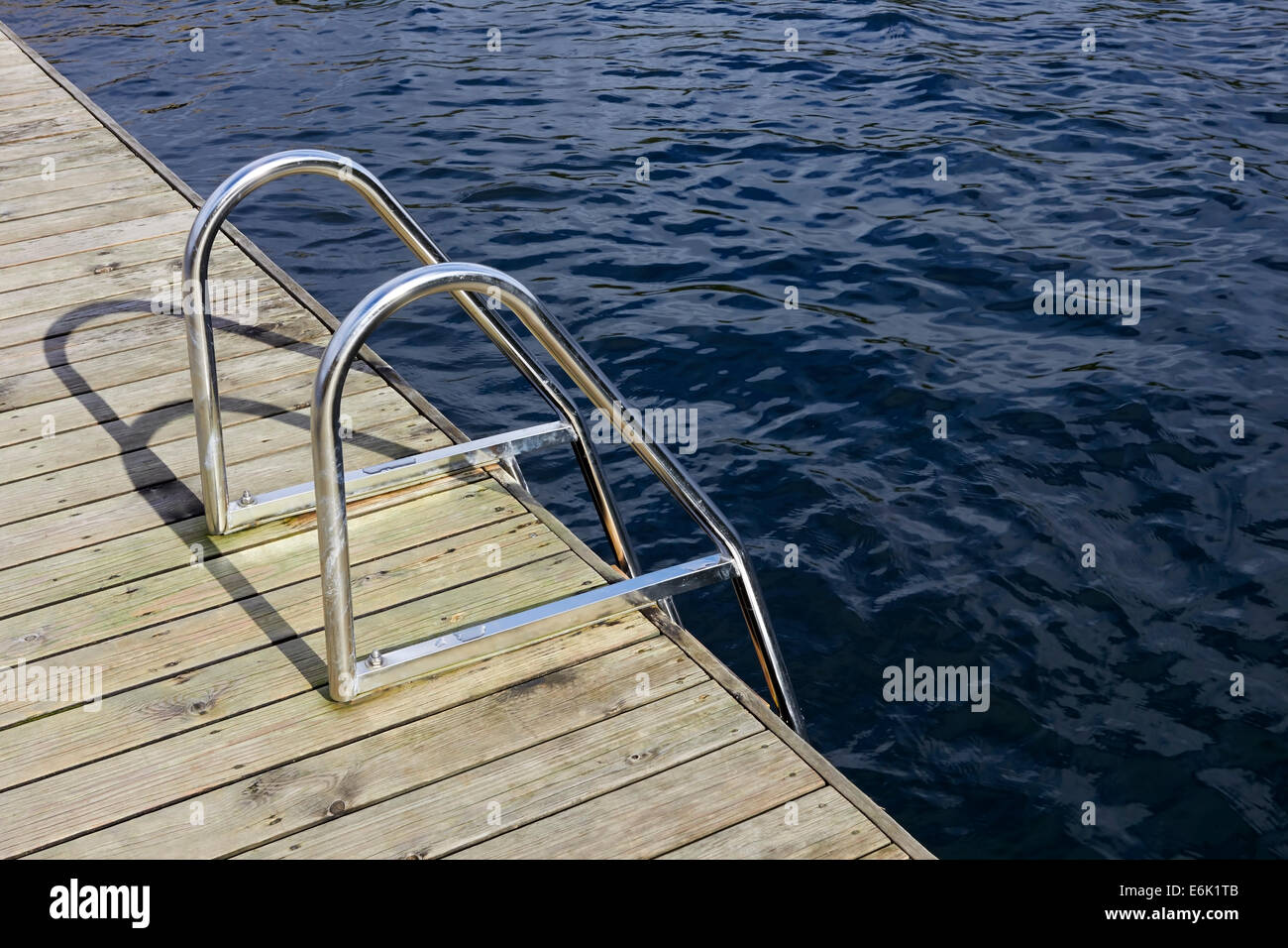 handrails and ladder on wooden jetty Stock Photo