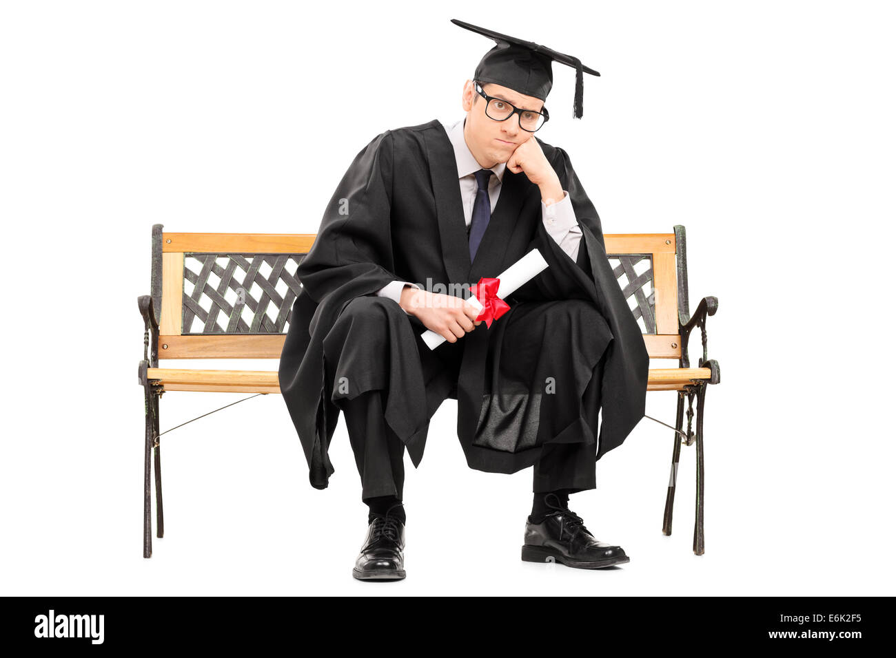 Angry college graduate holding a diploma isolated on white background - Stock Image