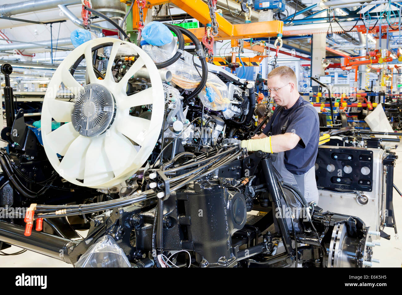 Employee installing the engine and transmission in a chassis at MAN Truck and Bus AG, Munich, Upper Bavaria, Bavaria, - Stock Image