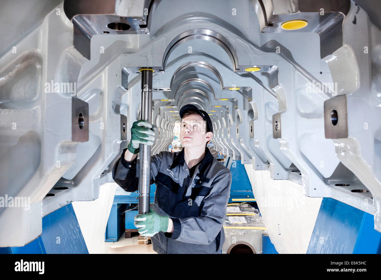 Employee fitting a tension rod into the engine frame of a marine engine, MAN Diesel and Turbo SE, Augsburg, Bavaria, - Stock Image