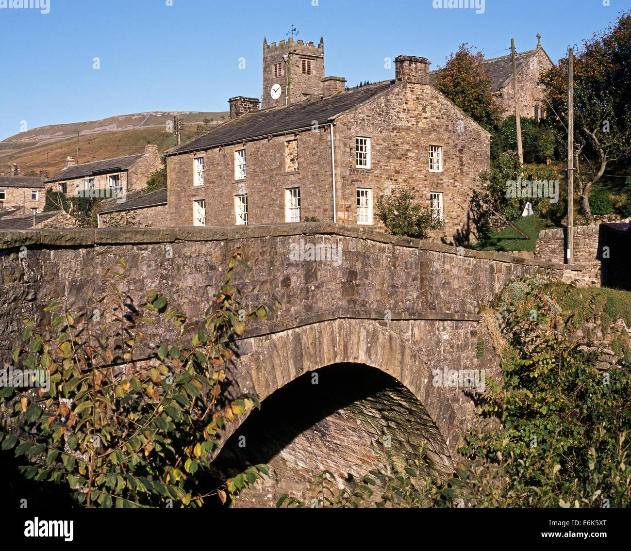 Stone road bridge over Straw Beck with village and church to rear, Muker, Swaledale, Yorkshire Dales, North Yorkshire, - Stock Image