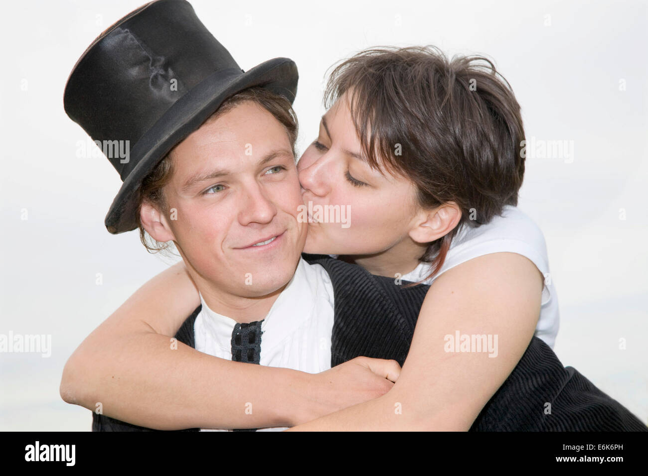 Young man wearing a top hat being tenderly kissed by his partner as he carries her piggyback Stock Photo