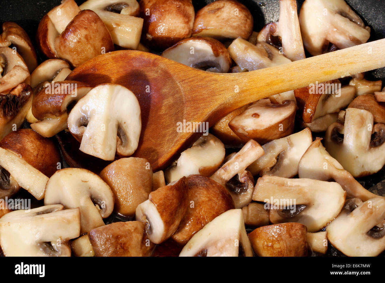 Sliced mushroom in a pan with a wooden spoon - Stock Image