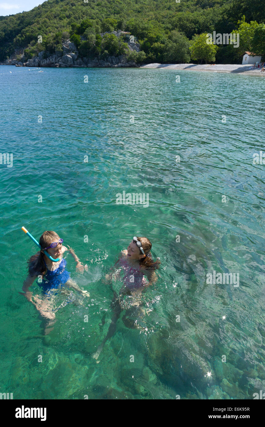 Children swimming and snorkeling in the bay near Porozina village at the north end of the island of Cres, Croatia - Stock Image