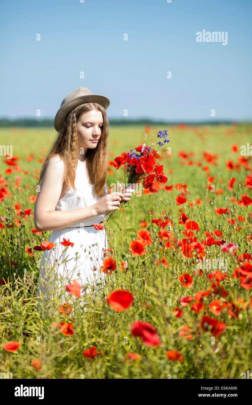 Young woman at white dress collects poppy bouquet - Stock Image
