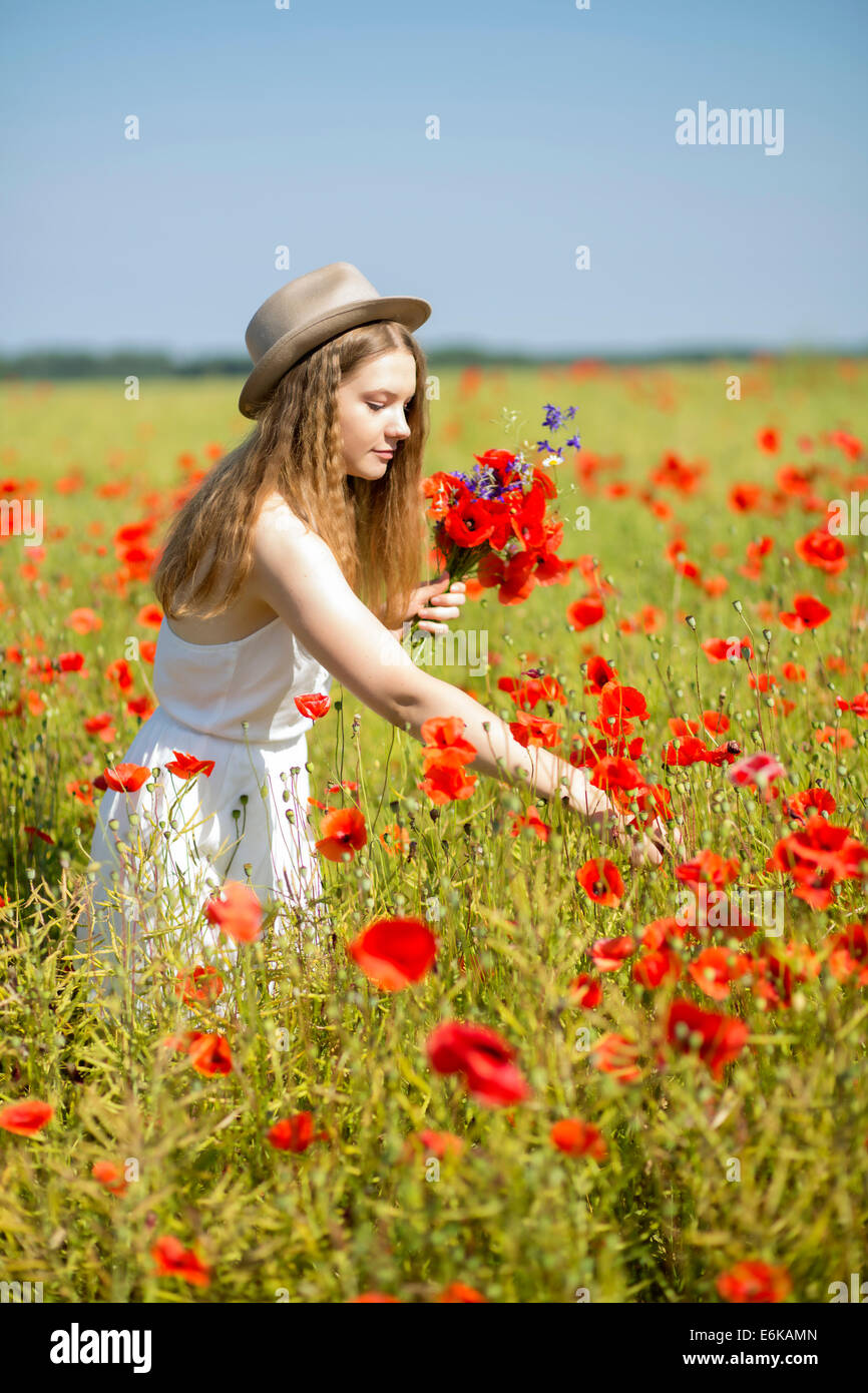 Young woman at white dress collects nice bouquet - Stock Image