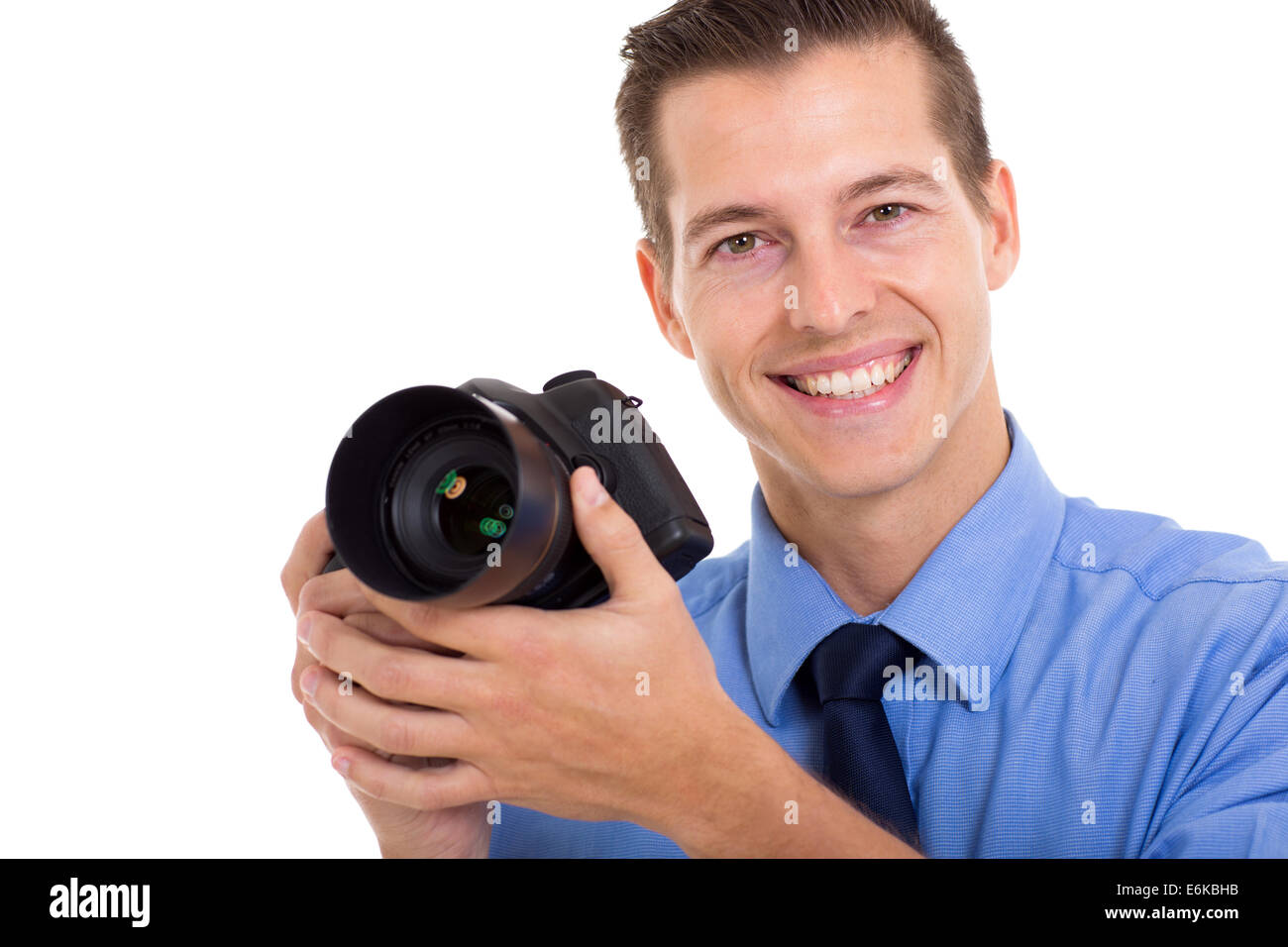 cheerful photographer holding a DSLR camera isolated on white - Stock Image