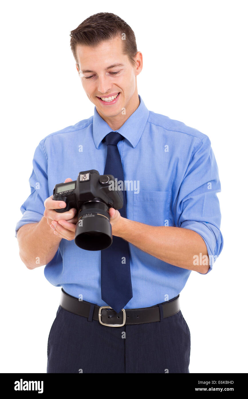 handsome photographer checking photos on his camera isolated on white background - Stock Image
