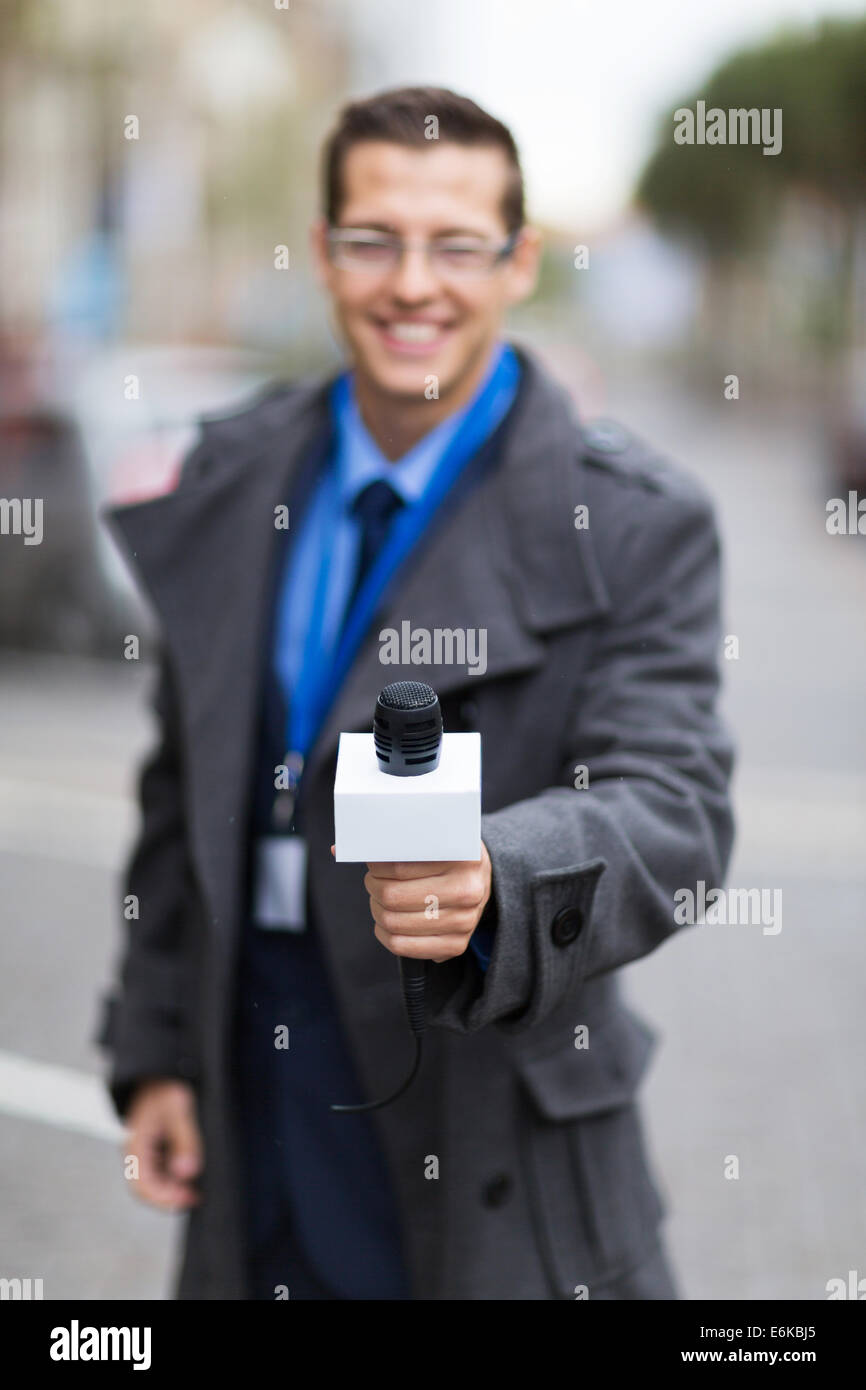 professional news reporter doing interview outdoors - Stock Image