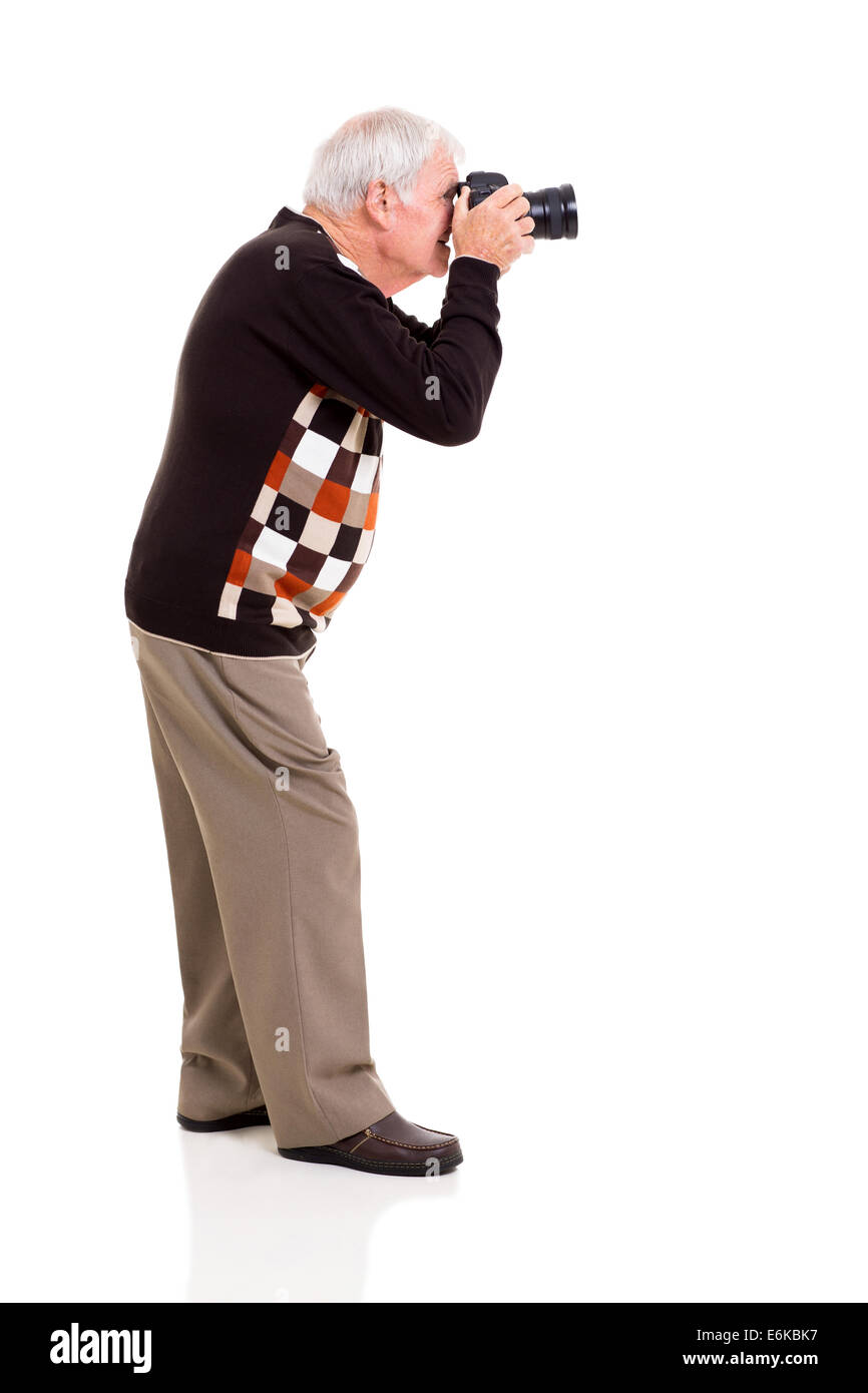 side view of elderly man shooting with digital SLR camera on white background - Stock Image
