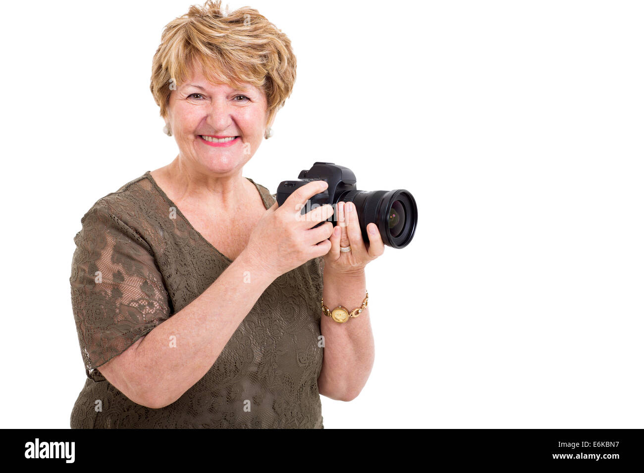 cheerful senior woman holding a digital SLR camera over white background - Stock Image