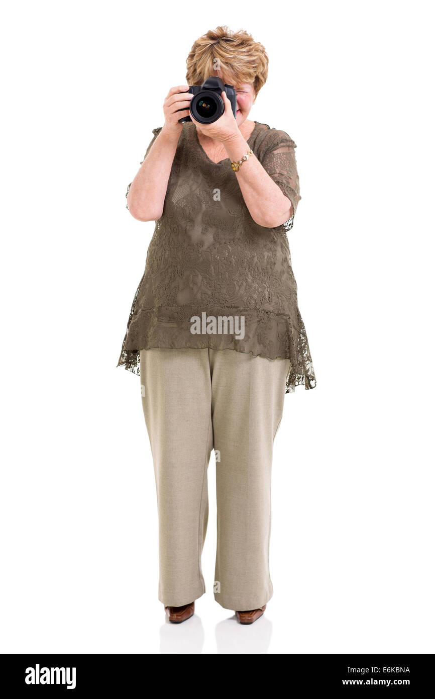 elderly woman shooting pictures with digital SLR camera on white - Stock Image